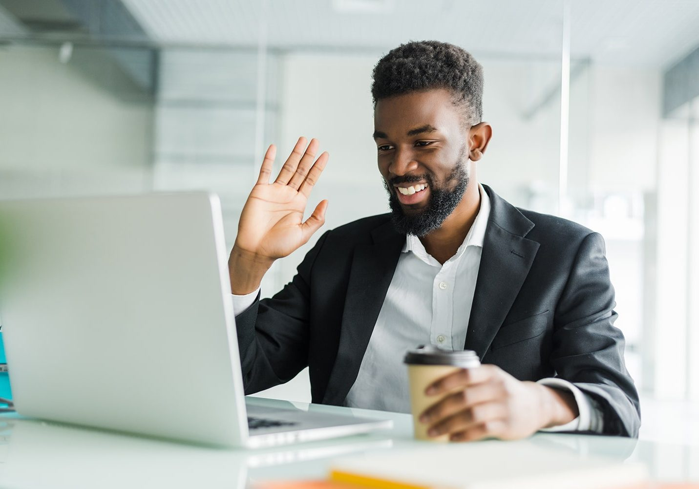 Young African manager with stubble sitting in front of open laptop wearing earphones while having video conference call with business partners